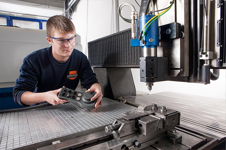 Auszubildender an der Fräsmaschine bei der Stempelproduktion